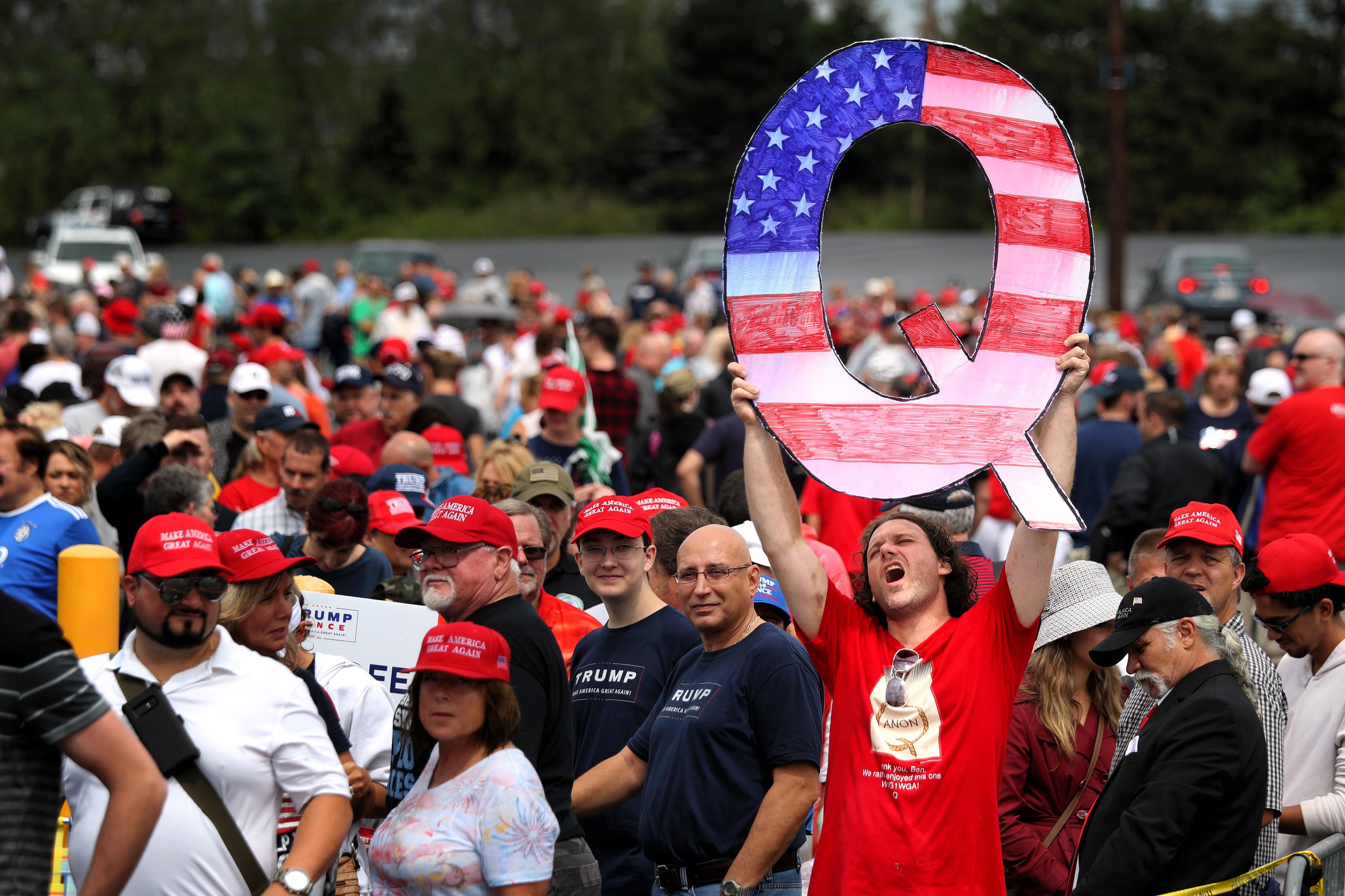 ペンシルベニアでの2018年の集会でドナルド・J・トランプ大統領に会うために並んで待っている間、デビッド・ライナートは大きな「Q」サインを掲げています。
