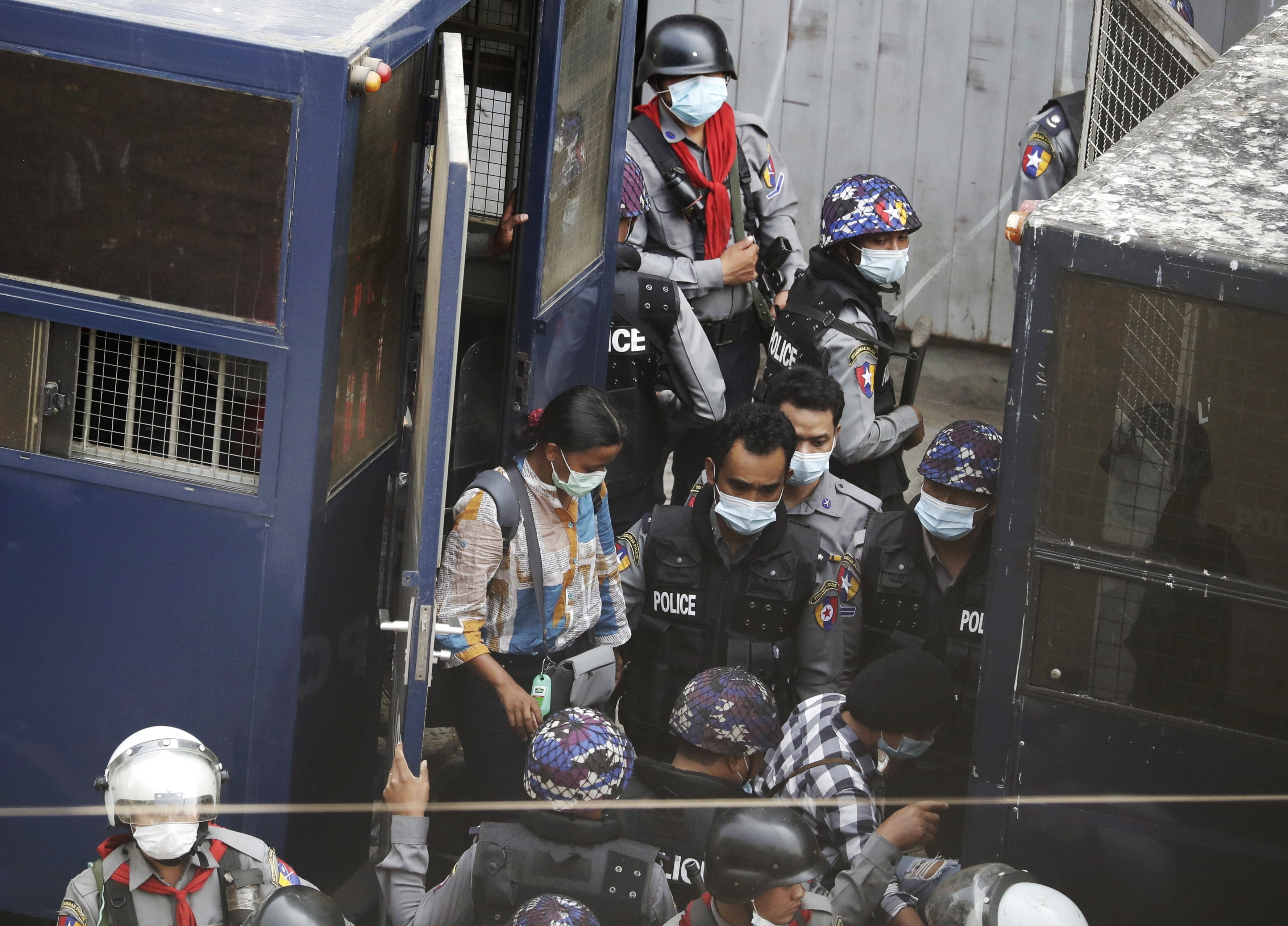 Police transfer arrested Myanmar journalist Kay Zun Nway from a police vehicle to another during a protest against the military coup in Yangon.