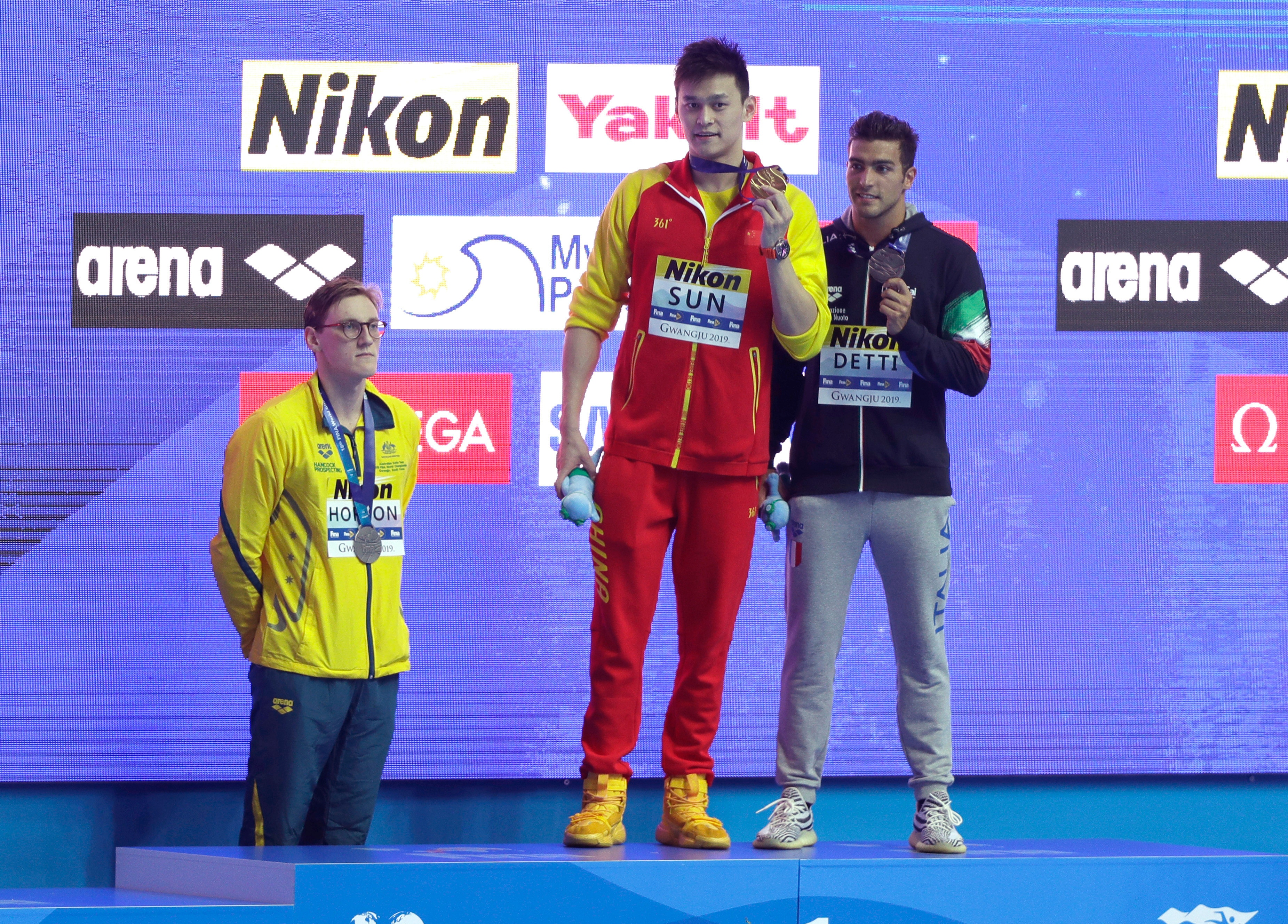 China's Sun Yang holds up his gold medal as silver medalist Australia's Mack Horton, left, stands away from the podium at the World Swimming Championships.