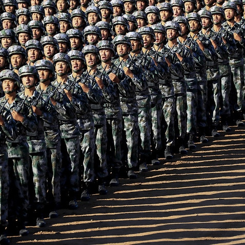 In this photo released by China's Xinhua News Agency, Chinese People's Liberation Army (PLA) troops march in formation Sunday, July 30, 2017