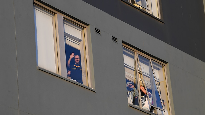 Detainees are seen through a window of the Mantra Hotel during a candlelight vigil in Preston, Melbourne, last week.