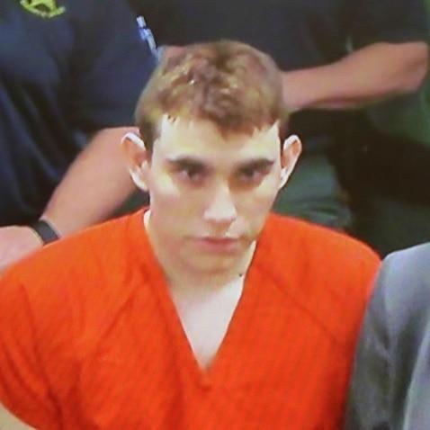A video monitor shows school shooting suspect Nikolas Cruz, center, making an appearance before Judge Kim Theresa Mollica in Broward County Court