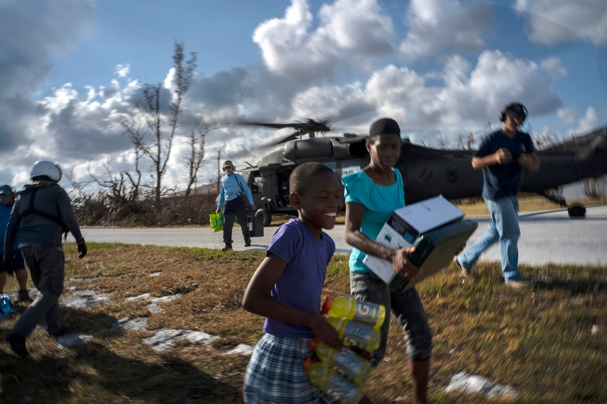 Ayfon Minus, 8, collects food taken by helicopter from the capital to the village destroyed by Hurricane Dorian In High Rock, Grand Bahama.