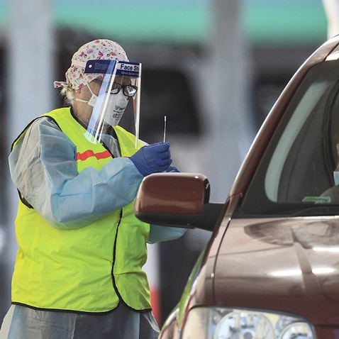 A person receives a COVID test in their car at a drive-through testing site at Shepparton Greyhound and Trotting Track in Shepparton, Victoria