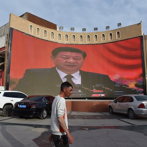 A man walking past a screen showing images of China's President Xi Jinping in Kashgar in China's northwest Xinjiang region.