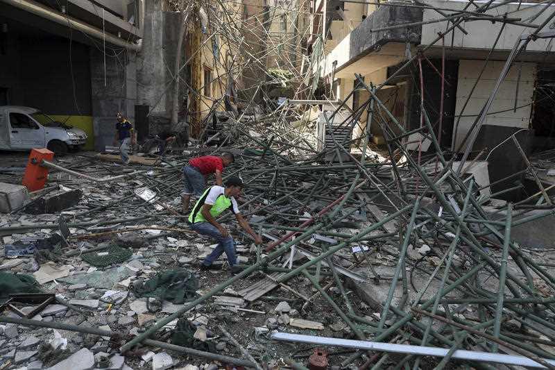 2020年8月6日(木)、レバノンのベイルートの港を襲った火曜日の爆発の場所の近くの損傷した建物から労働者が瓦礫を取り除く