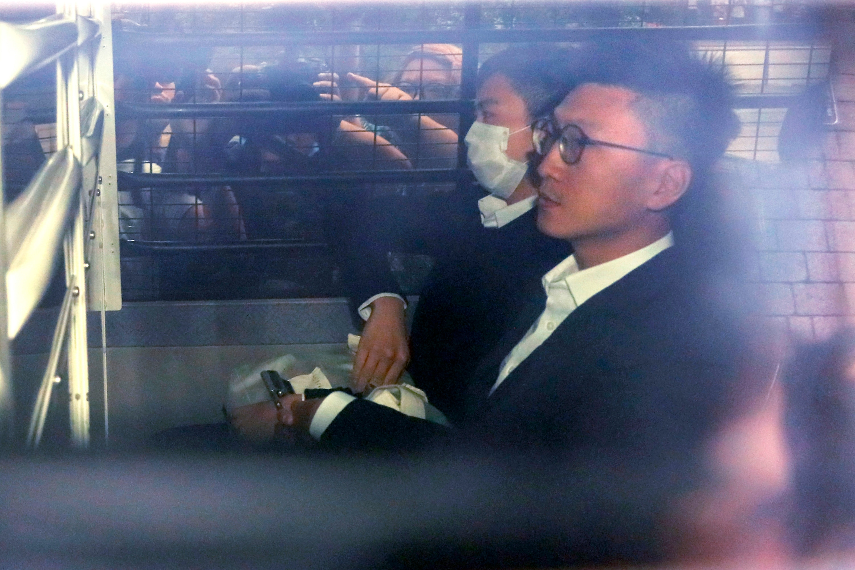 Hong Kong Jailed activist Edward Leung, right, is escorted by Correctional Services officers in a prison van as he arrives high court for his sentence appeal.