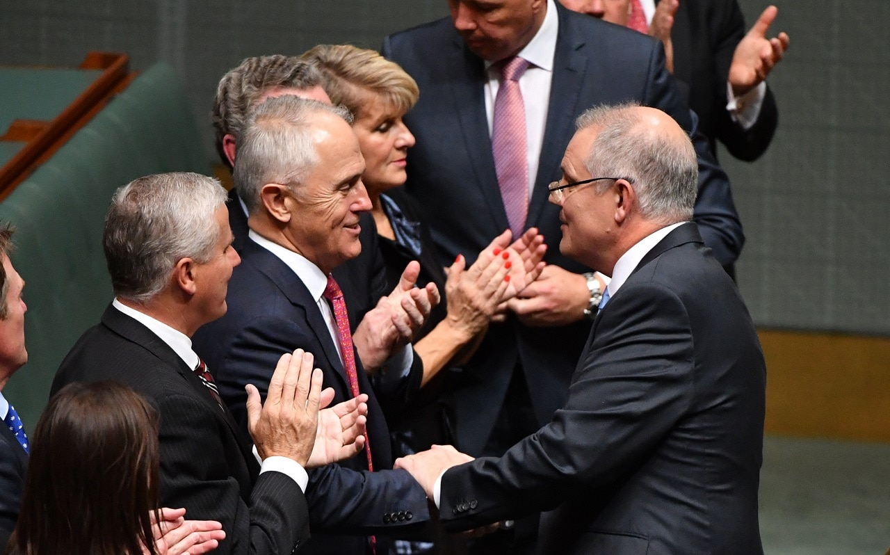 Prime Minister Malcolm Turnbull shakes hands with Treasurer Scott Morrison after delivering the 2018 Budget in the House of Representatives at Parliament House in Canberra, Tuesday, May 8, 2018. (AAP Image/Mick Tsikas) NO ARCHIVING