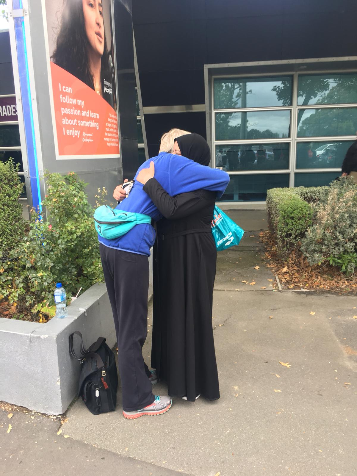 Mourners hug outside the Al Noor mosque on Saturday.