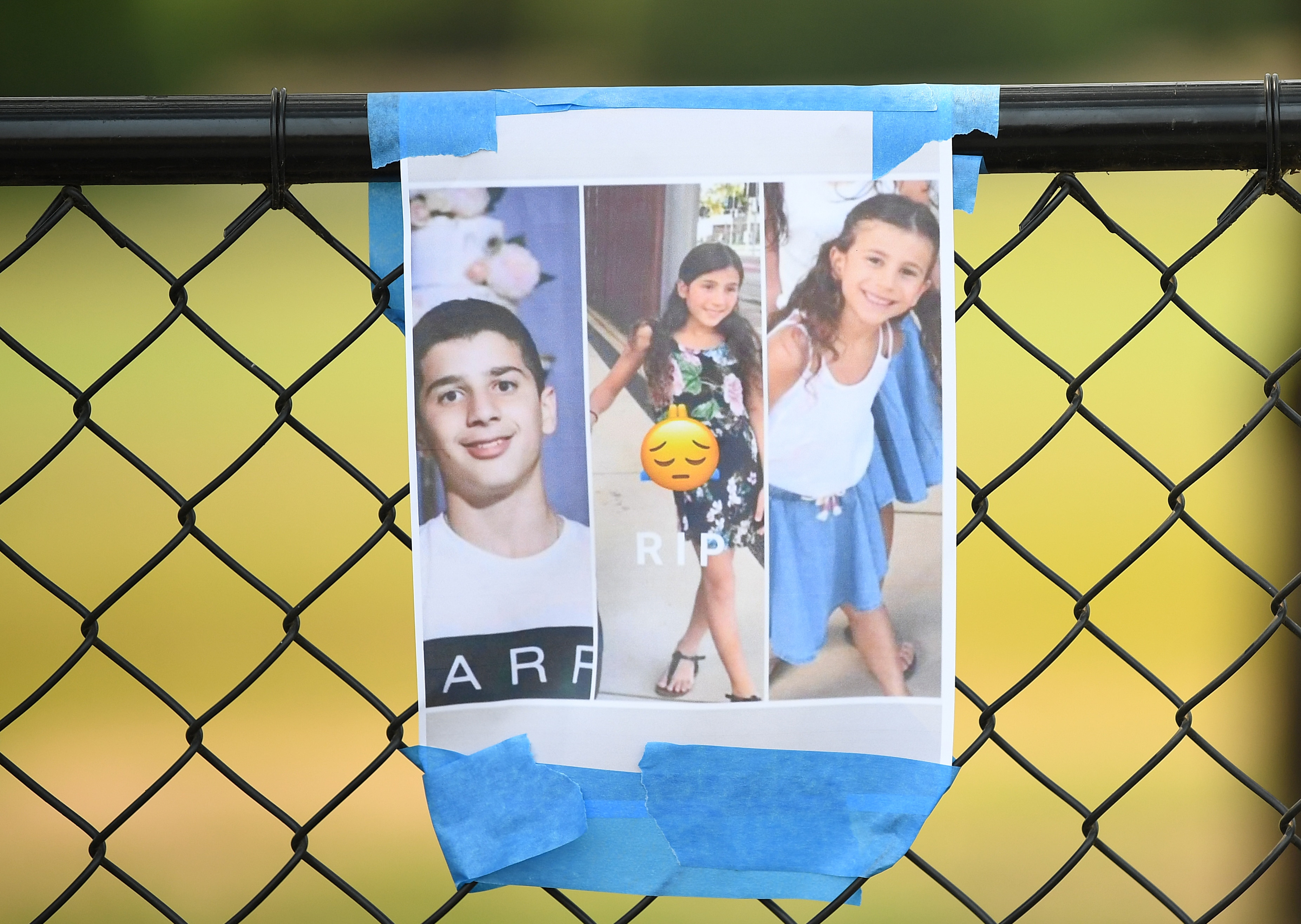 Photos of three victims were hung among a floral tribute at the scene of the crash.
