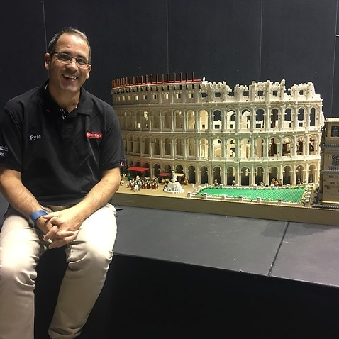 Ryan McNaught sits next to a lego model of the ancient Roman colosseum at a lego exhibition on the Gold Coast