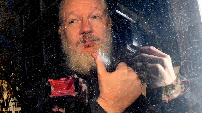 Julian Assange gestures as he arrives at Westminster Magistrates' Court following his arrest