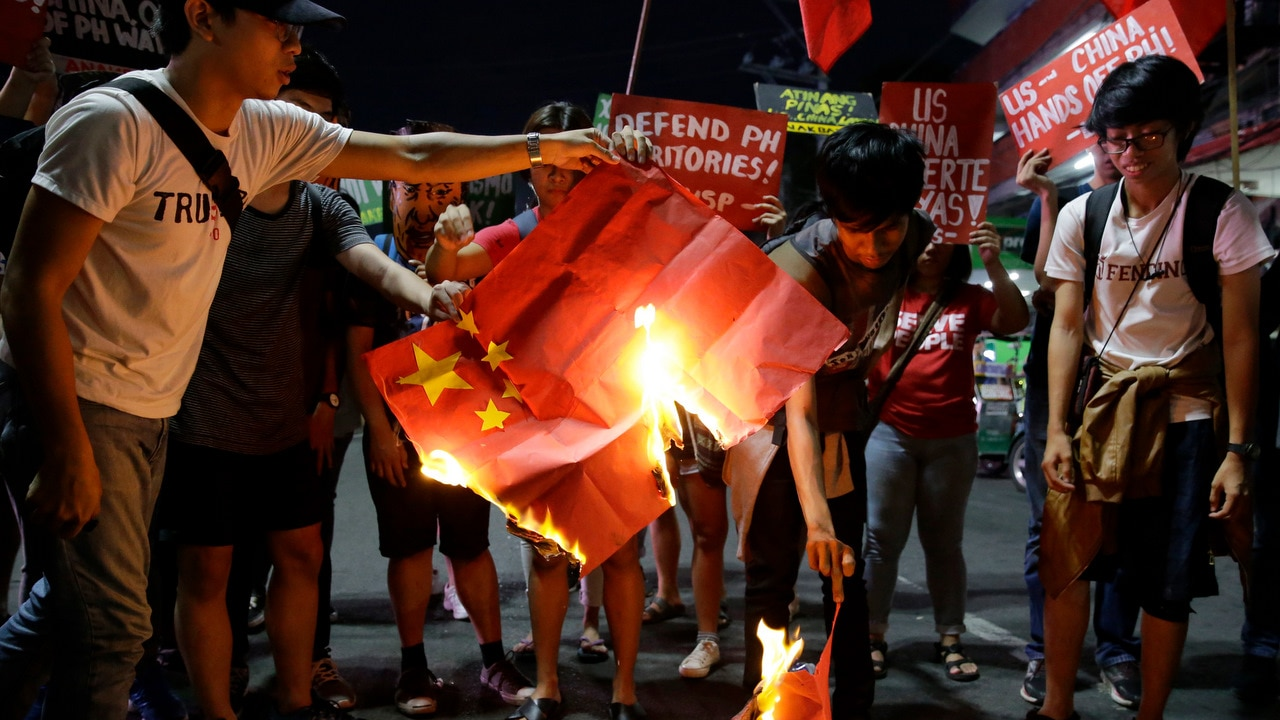 Student rallyist burn a Chinese flag as they protest against the visit of Chinese President Xi Jinping.