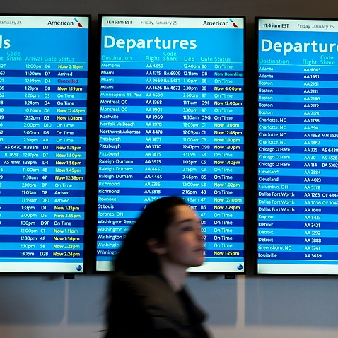 A person walks past a board showing departure and arrival times at LaGuardia airport in New York