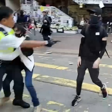 Hong Kong police officer shoots protester in street.