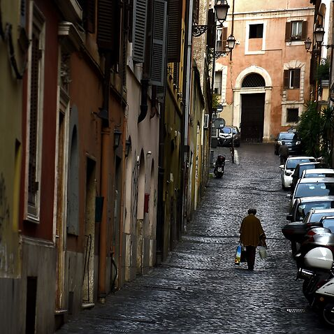 A woman walks in a narrow street of the Monti area, on October 26, 2016 in Rome.  / AFP / FILIPPO MONTEFORTE        (Photo credit should read FILIPPO MONTEFORTE/AFP/Getty Images)