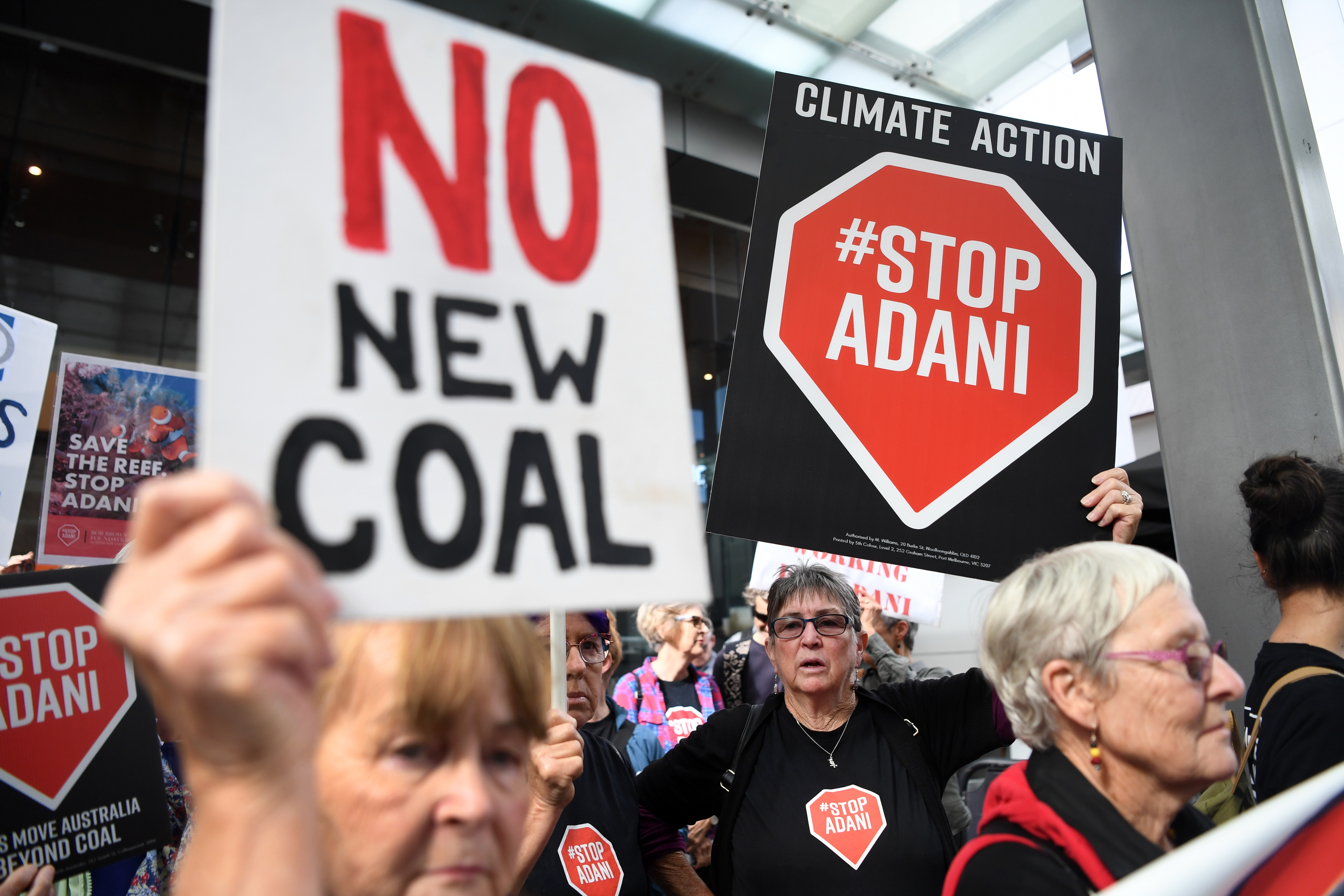 Anti-Adani protesters hold placards outside the offices of engineering and construction company GHD in Brisbane, Thursday, August 1, 2019. (AAP Image/Dan Peled) NO ARCHIVING