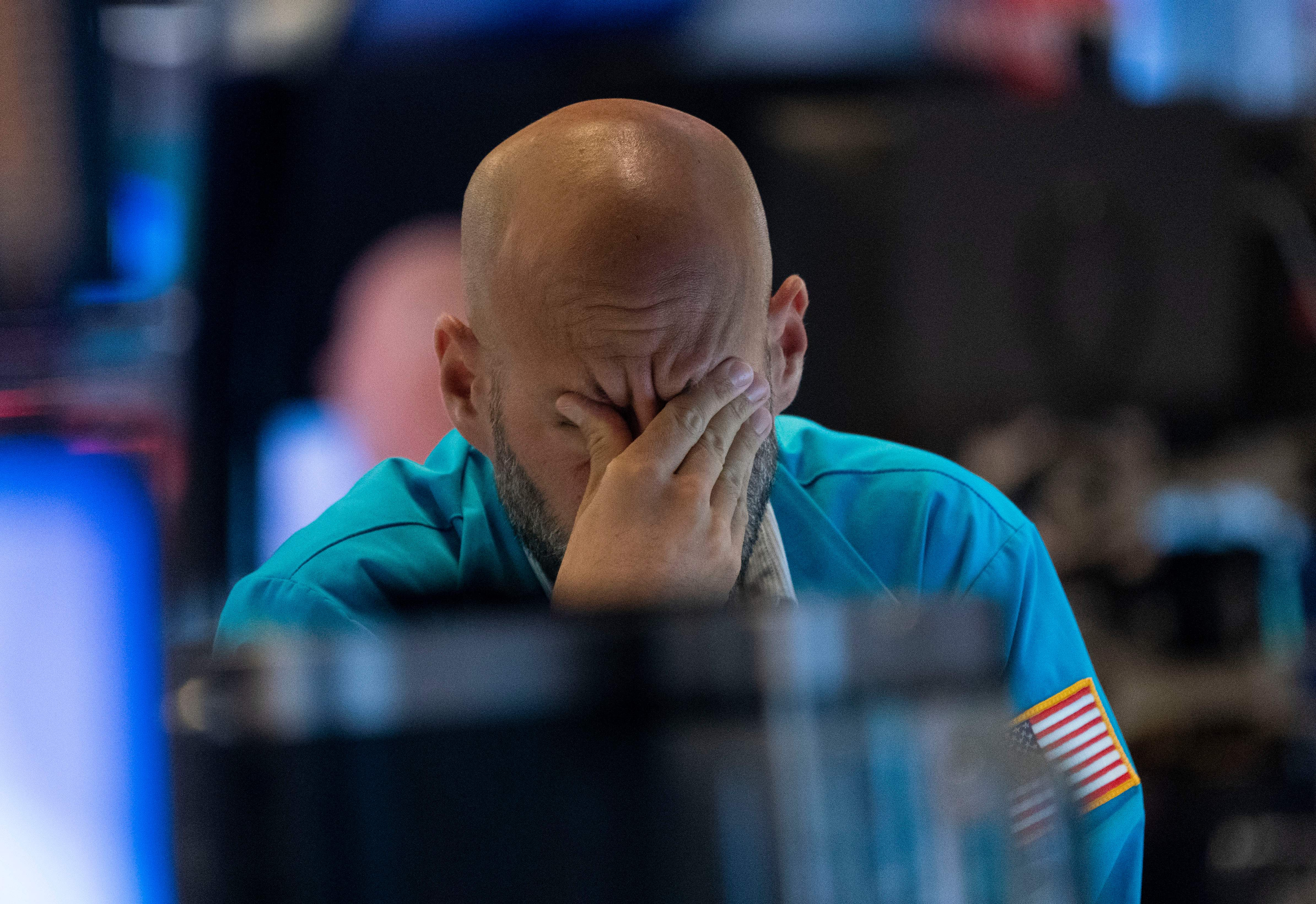 A trader wipes his eyes as he watches stock prices at the New York Stock Exchange.