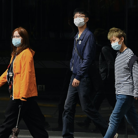 Pedestrians seen wearing a face masks in Sydney.