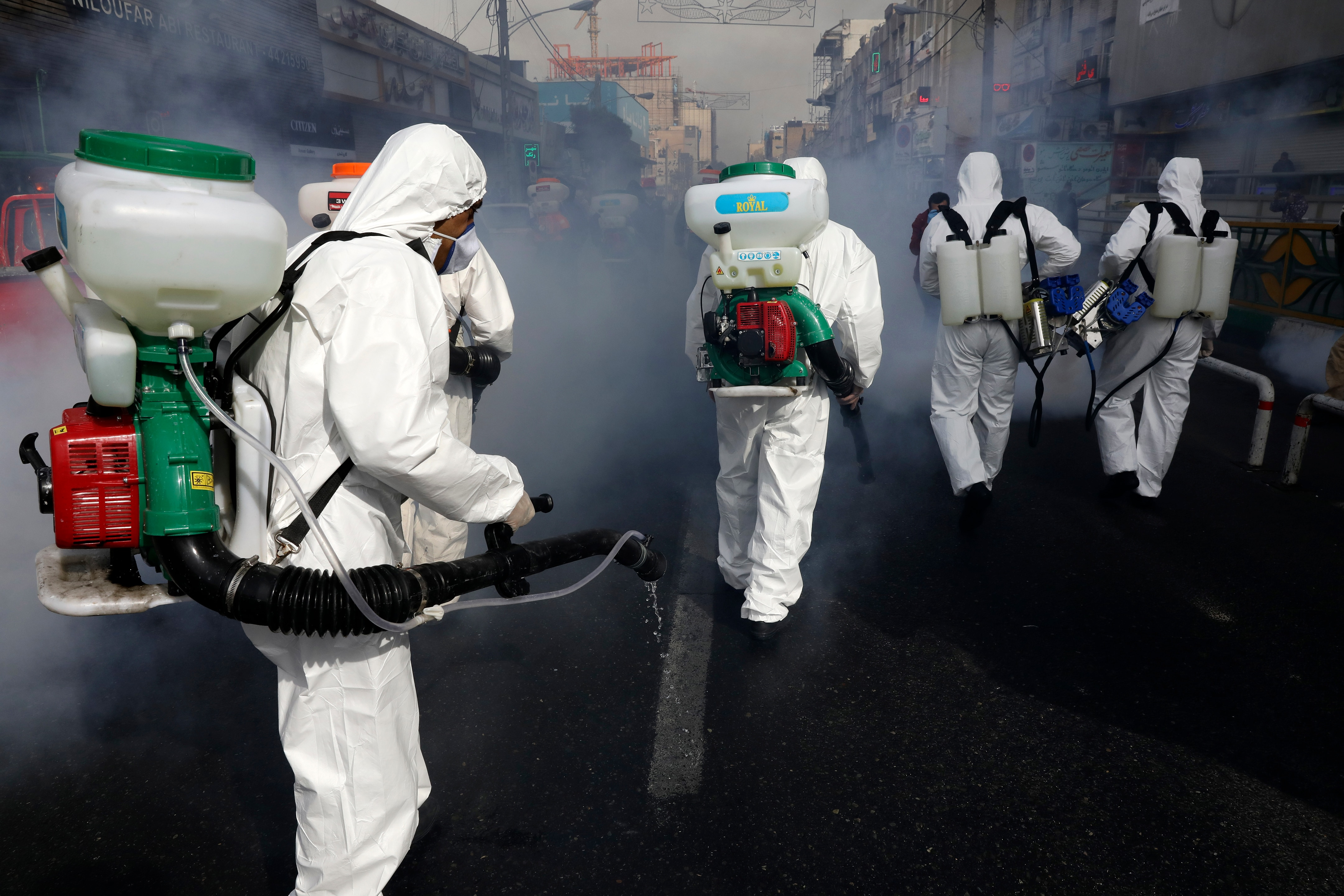 Firefighters disinfect a street against the new coronavirus, in western Tehran, Iran.