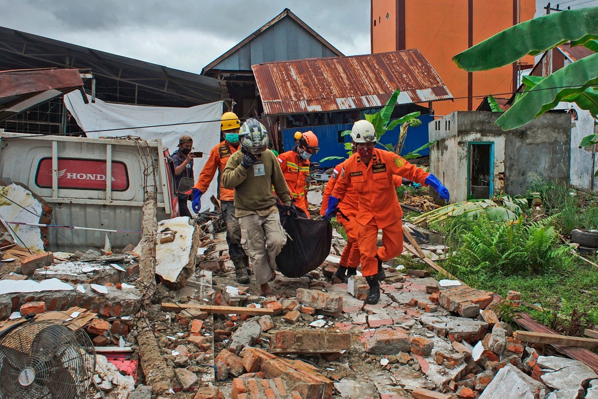 Recuers carry a body bag containing a victim of an earthquake in Mamuju, West Sulawesi, Indonesia.