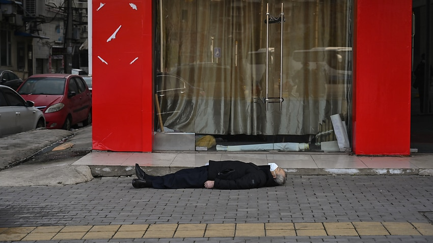 An elderly man wearing a face mask lying on the pavement after he collapsed and died near a hospital in Wuhan.