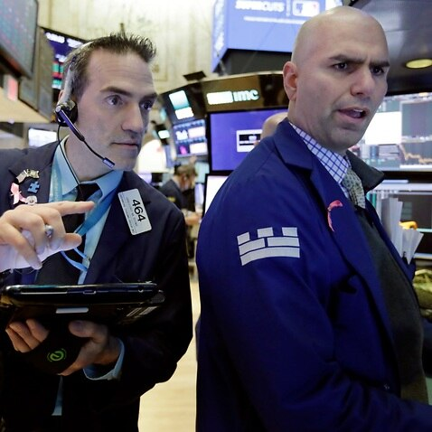 Trader Gregory Rowe, left, and specialist Philip Finale work on the floor of the New York Stock Exchange