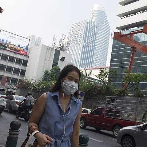 A woman wears a face mask on the way to work while smog blankets Bangkok.