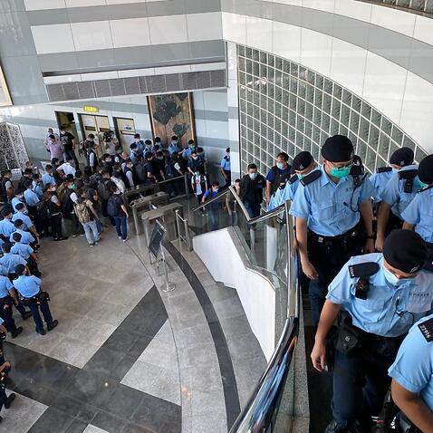 Scores of Hong Kong police raid the Apple Daily newspaper in Hong Kong.