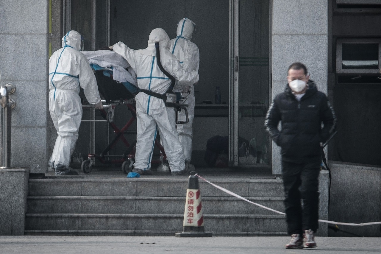 Medical staff members carry a patient into the Jinyintan hospital, where patients infected by the SARS-like virus are being treated