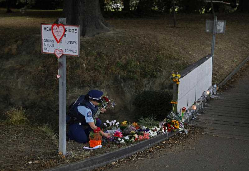 A police officer drops off flowers at a park outside the Masjid Al Noor mosque in Christchurch ahead of the funeral.