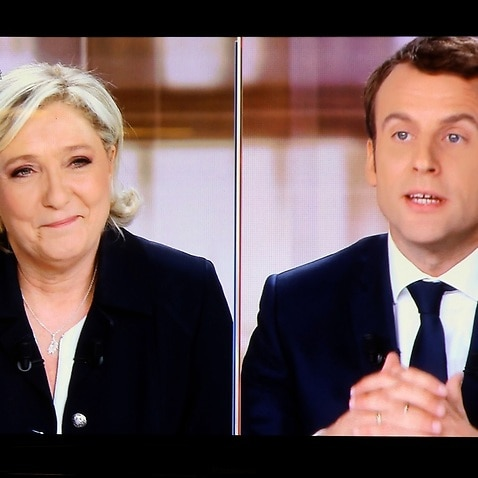 A television screen shows the live broadcast television debate with French centrist presidential candidate Emmanuel Macron, right, and Marine Le Pen