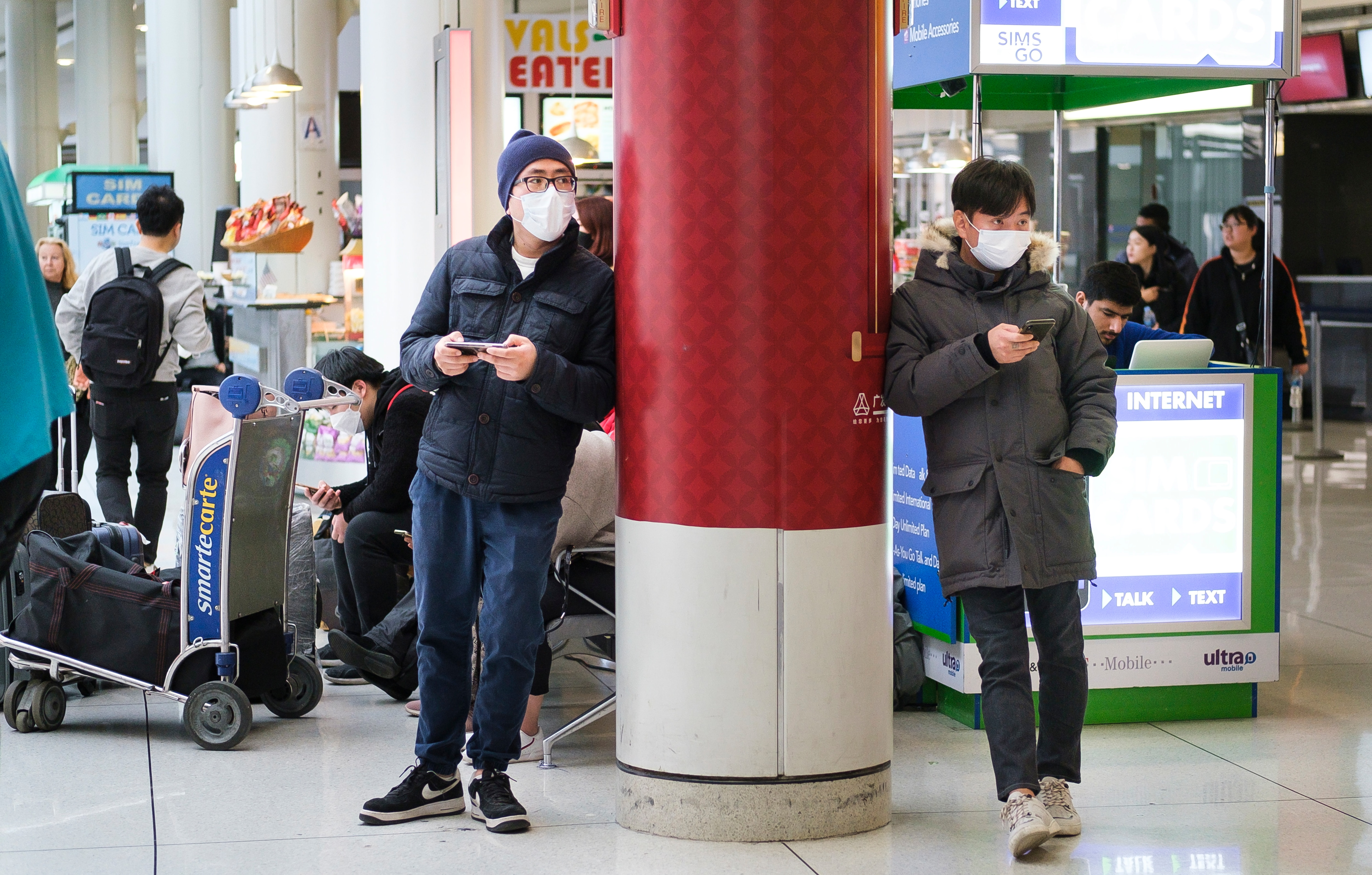 People wearing medical masks wait for arriving passengers at John F. Kennedy international airport in New York.