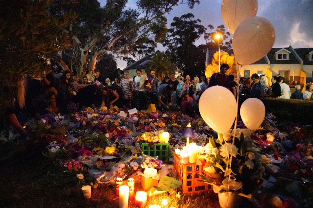 The site where the body of Aiia Maasarwe was found is surrounded by mourners and flowers in Bundoora.