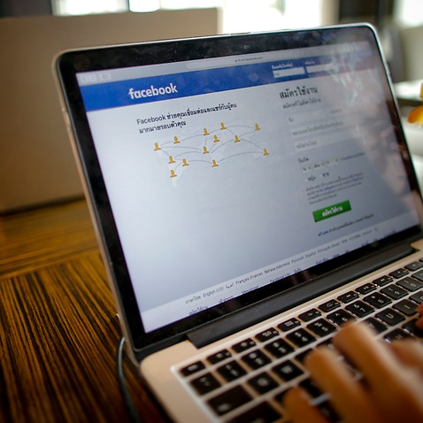 A person uses a computer displaying the Thai Facebook