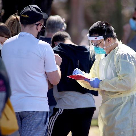 2020年11月17日、アデレードのパラフィールド空港にあるCOVID-19検査施設で列に並んでいる人々から詳細を取得する医療スタッフ。