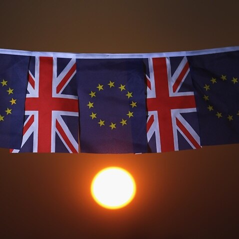 A file image of the sun sets behind European Union and the Union flag