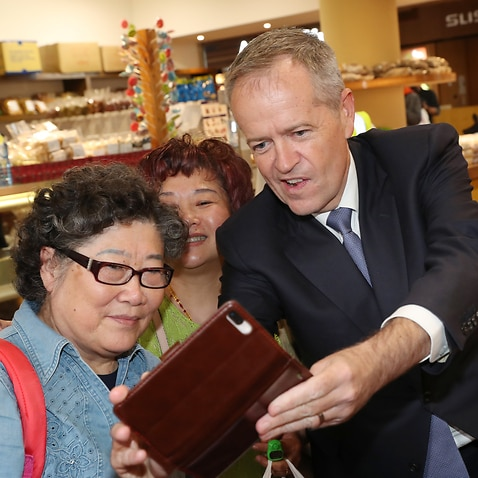 Opposition Leader Bill Shorten (centre) and Labor candidate for Chisholm Jennifer Yang (right) pose for a photograph during a visit to Box Hill Central Shopping Centre in Melbourne, Saturday, April 6, (AAP Image/David Crosling) NO ARCHIVING