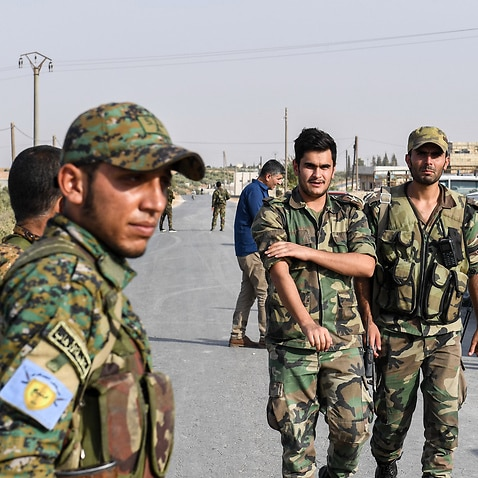 A fighter (L) bearing the insignia of the Manbij Military Council stands by as Syrian government soldiers walk past.