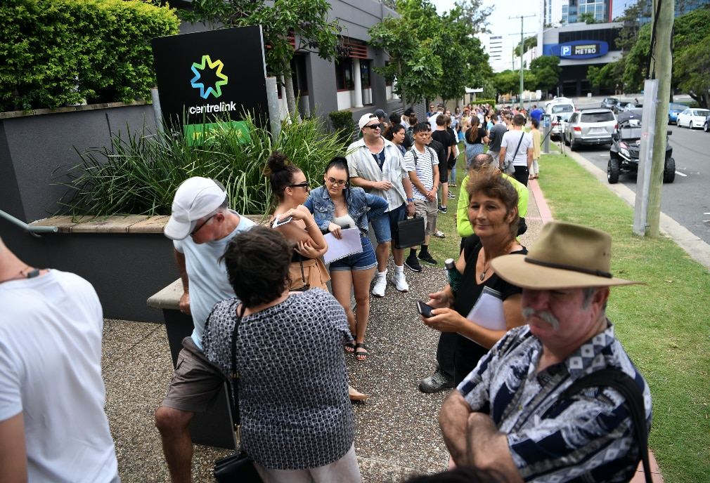 People are seen queueing outside the Centrelink office in Southport on the Gold Coast.