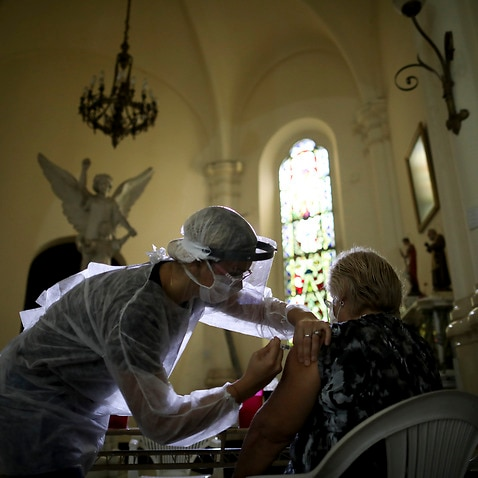 A medical worker administers a flu vaccine inside a church as part of a government vaccination campaign, in Buenos Aires, Argentina, Saturday, April 11, 2020.