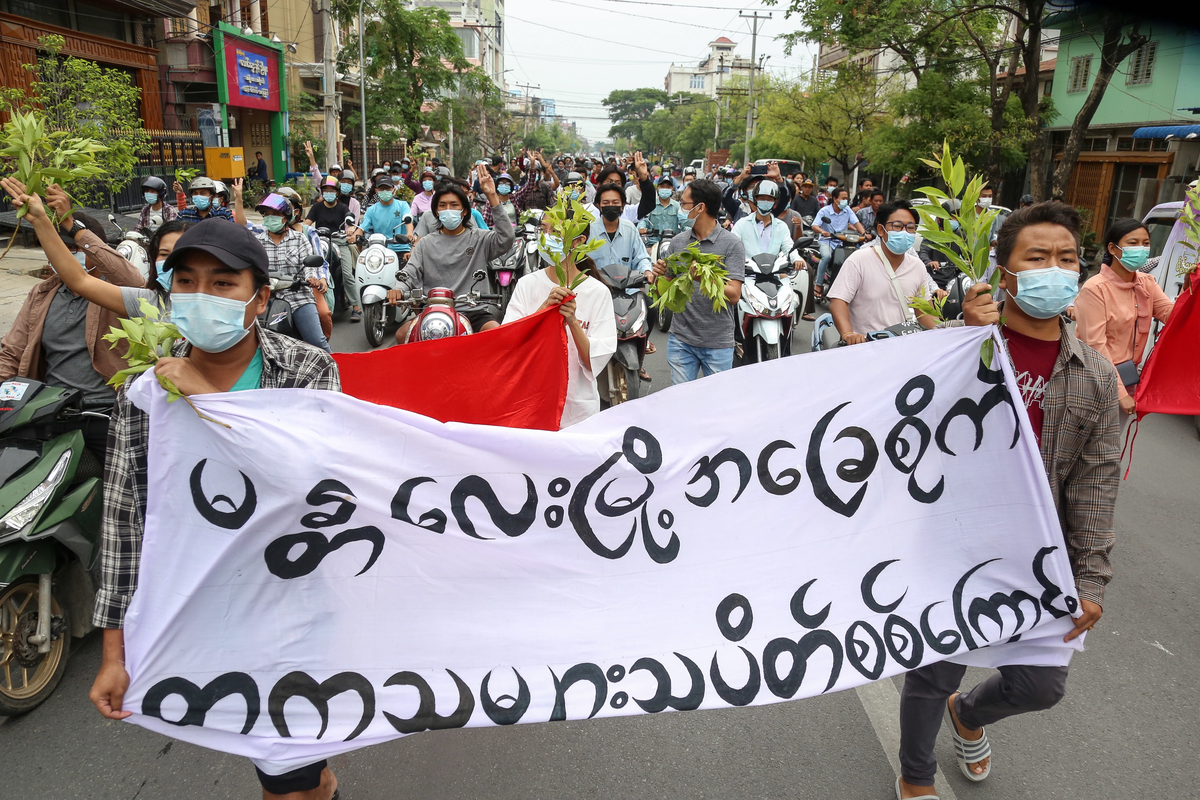 Demonstrators carry a banner during an anti-military coup protest in Mandalay, Myanmar, on 17 April, 2021.