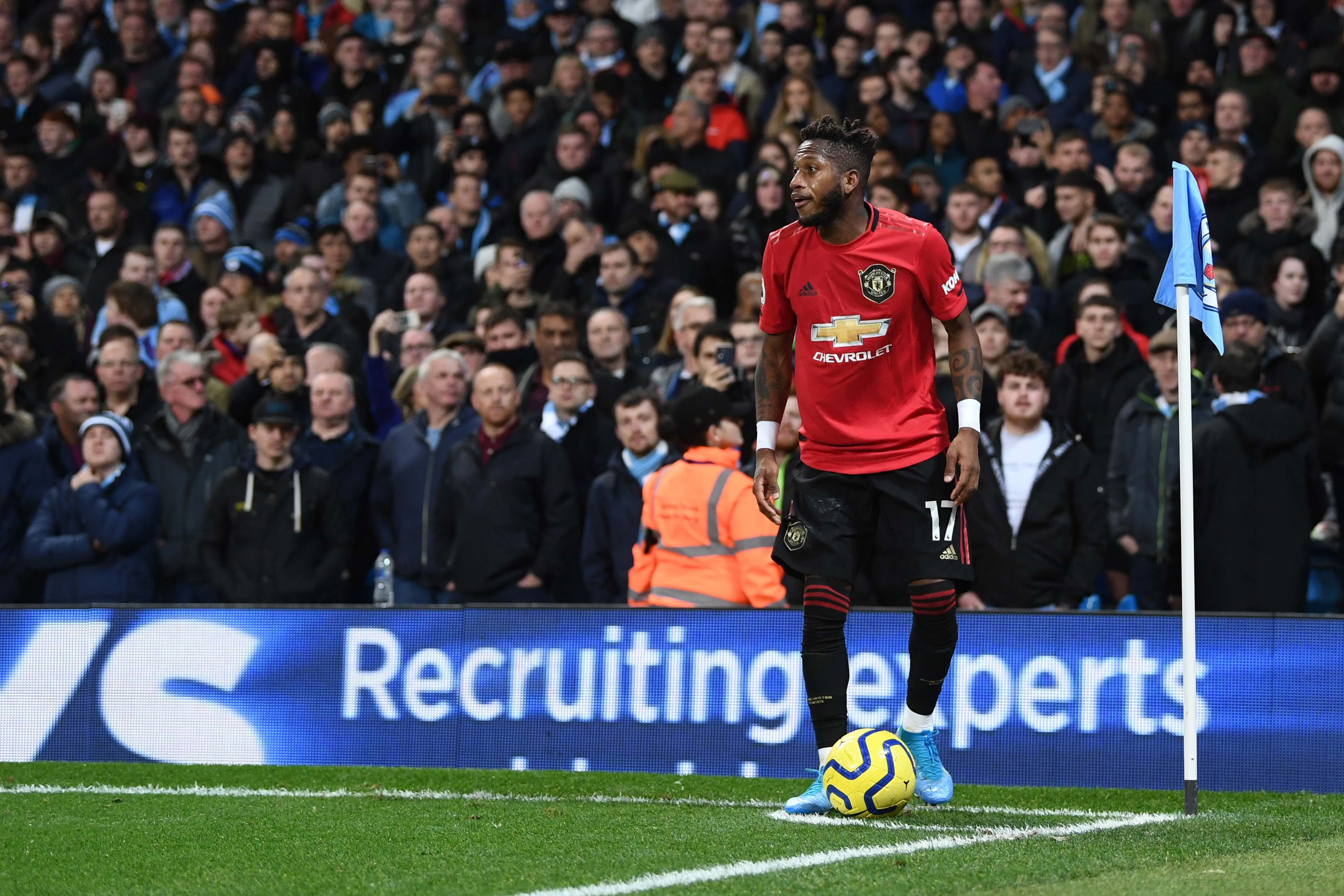 Fred of Manchester United takes a corner kick after being hit by objects thrown by the Manchester City fans during the Premier League derby at Etihad Stadium.