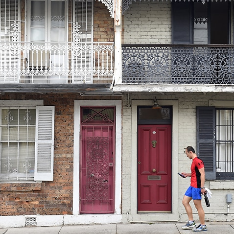 A man walks past some residential houses.
