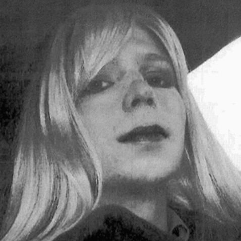 Chelsea Manning poses for a photo wearing a wig and lipstick