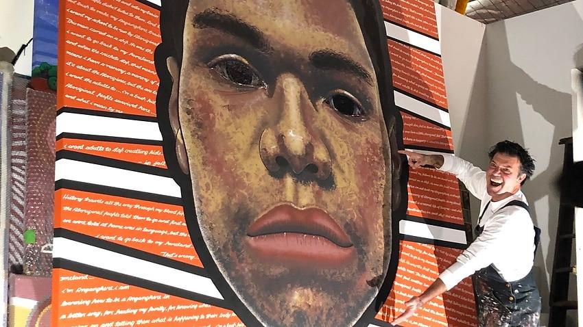 Blak Douglas with his finished portrait of Dujuan Hoosan.