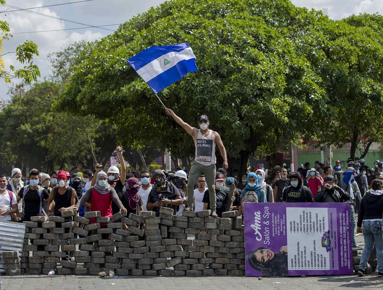 A young man raises a Nicaraguan national flag on a cobblestone barricade in Managua, Nicaragua, on April 21.