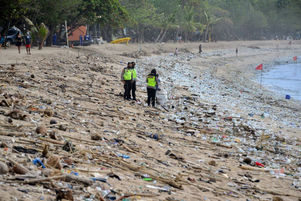 Police stand amongst rubbish washed up on Kuta beach on Indonesia's tourist island of Bali 31 December 2020.