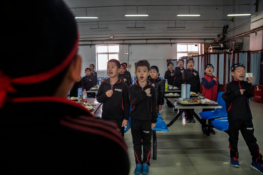 Students at the Real Boys Club recite the club's pledge in Beijing.