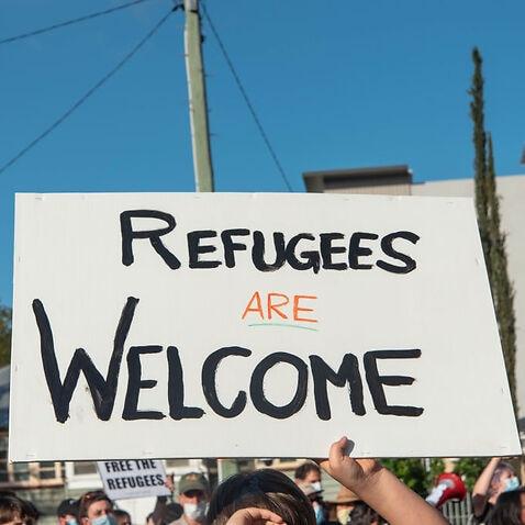 抗議者は「難民は大歓迎です」という看板を持っています